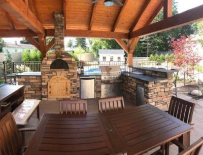 Masonry outdoor kitchen with pizza oven, stainless grill, fridge, and drawers with bar top